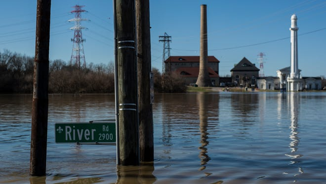 The River Road sign sits just above water in Louisville, Kentucky after weekend flooding led to the highest point for the Ohio River's waters Monday. Feb. 26, 2018