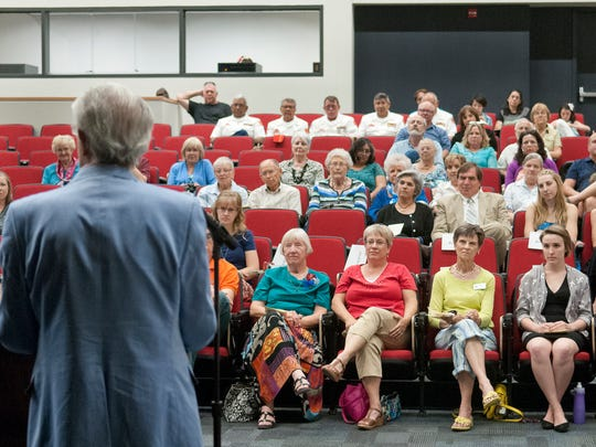 Playwright Mark Medoff speaks to a crowd gathered in the Robert L Gaines Theatre for the dedication Monday. Gaines' family members sit in the front row, from left: Carol Gaines, wife, and Lucy Rathgeber, daughter.