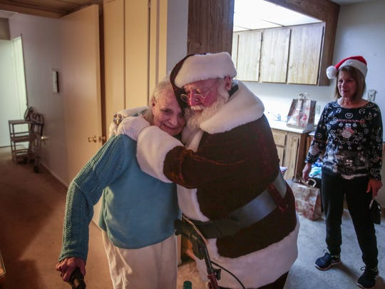 Bob Elias, the director of social services and Meals on Wheels for the Joslyn Center in Palm Desert, dressed as Santa, gives  Leona Bennett, 94, a hug and a gift of a disaster preparedness kit during a Meals on Wheels food delivery on Thursday, December 22, 2016, in Palm Desert as volunteer Karen Burke looks on.