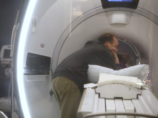 Paul Conrow leans in to hold Amanda's hand while she has a two-hour MRI scan.