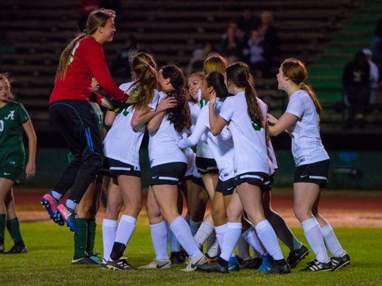 Lafayette High goalkeeper Katie Cook jumps onto the pile after her Lady Lions teammates scored a key goal during Tuesday's 2-2 tie against No. 1-ranked Acadiana.