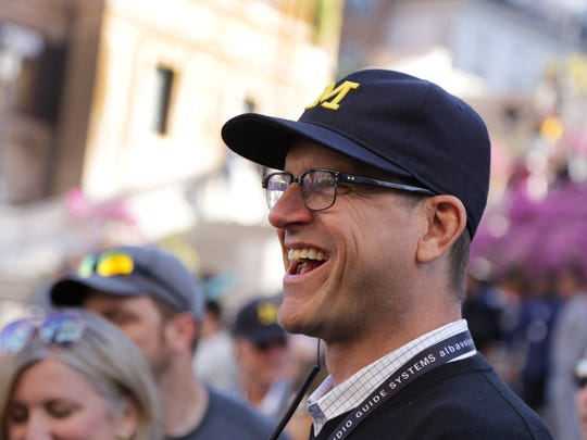 Michigan football coach Jim Harbaugh shares a laugh