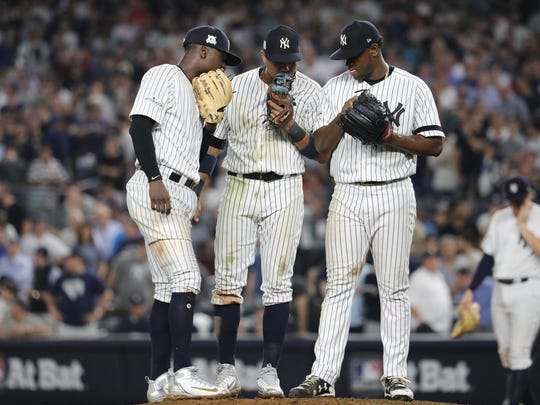 Didi Gregorius, Starlin Castro and Luis Severino meet at the pitchers mound, Monday, October 9, 2017.