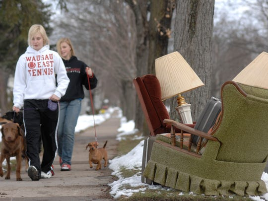 Butch McCartney/Wausau Daily HeraldSisters Ashley Katt, 14, left, and Emily, 12, walk their dogs passed items set out to be picked up on Monday in the city of Wausau's annual large item pick-up.