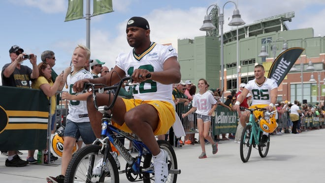 Green Bay Packers' Randall Cobb rides a bike to Friday's training camp practice.