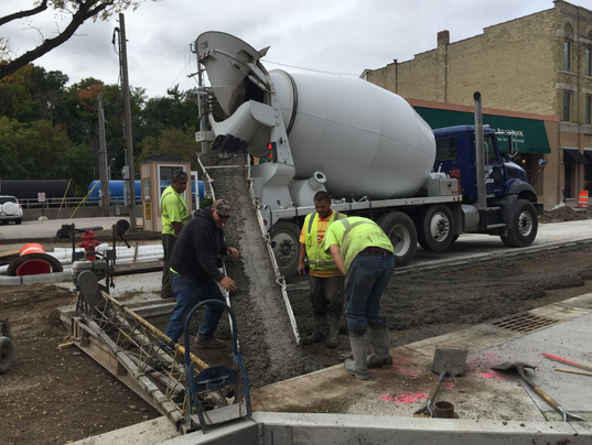 Workers pour concrete in the Village Improvement project.