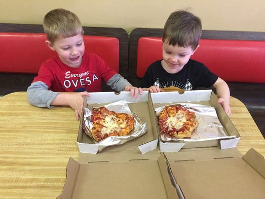 two child boys eating pizza