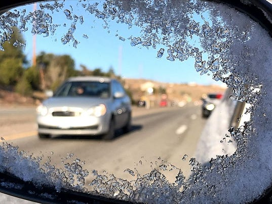 Snow on a side mirror showing traffic