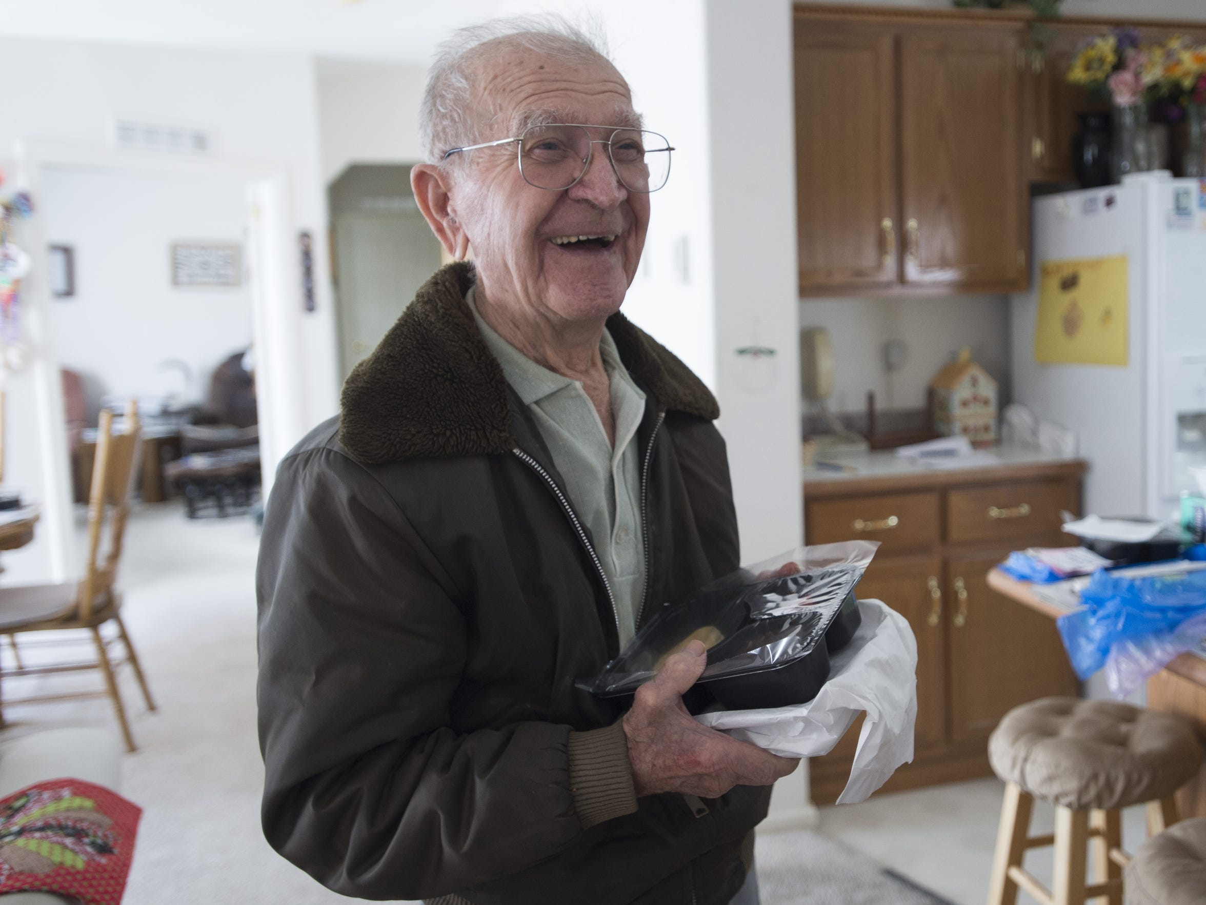 John Mihalek, 97, laughs during a meal delivery from Meals on Wheels at his home in east Fort Collins on Friday, March 17, 2017.