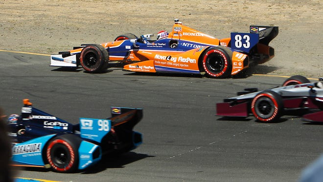 Charlie Kimball, of California, center, coasts to a stop after after colliding with another car during the Grand Prix of Sonoma IndyCar auto race.