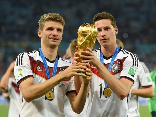 Germany midfielder Thomas Muller (13) and Germany midfielder Julian Draxler (14) celebrate with the world cup trophy after the championship match of the 2014 World Cup against the Argentina at Maracana Stadium. Germany won 1-0.