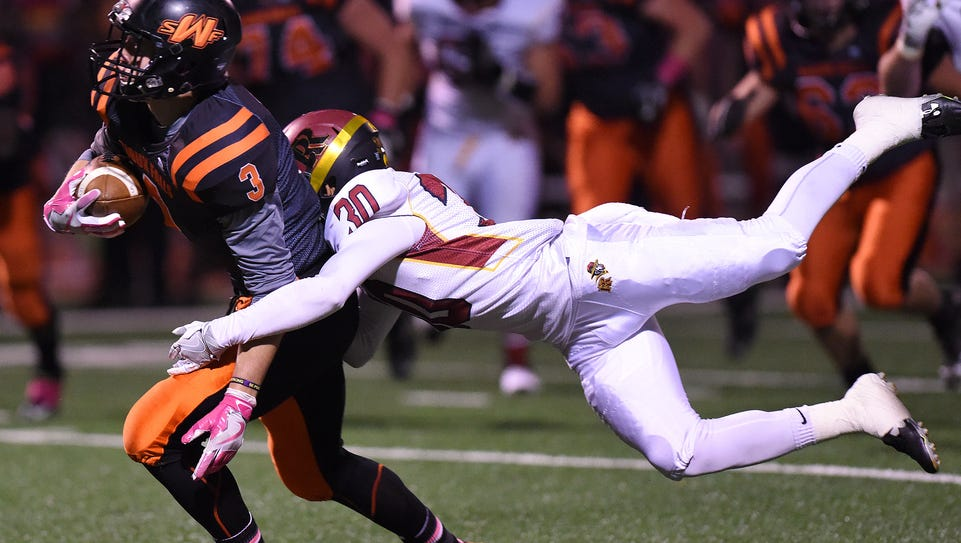 Washington's Logan Uttecht is tackled by Roosevelt's