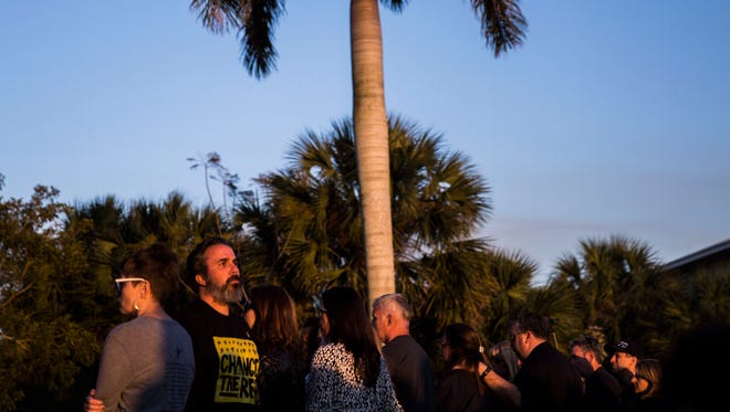 Manuel Oliver looks out over the memorials to the victims of the Marjory Stoneman Douglas High School shooting during a religious vigil at Pine Trails Park in Parkland, Fla., on Wednesday, March 14, 2018.