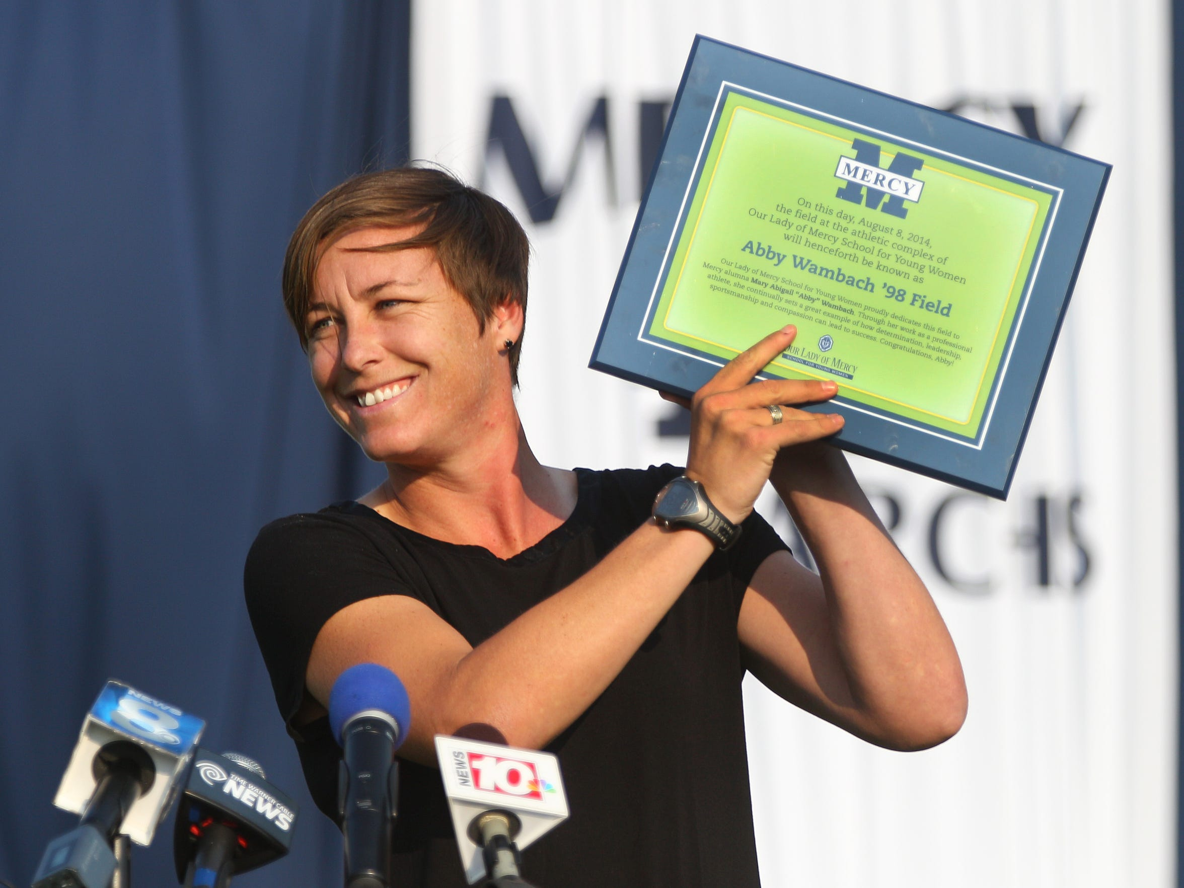 Abby Wambach displays a plaque she received after the soccer field at Our Lady of Mercy was named in her honor in 2014.