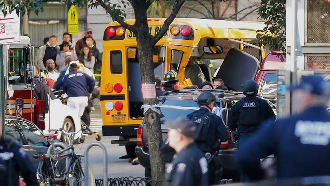 Authorities respond near a damaged school bus on Oct. 31, 2017, in New York. A motorist drove onto a busy bicycle path near the World Trade Center memorial and struck several people on Tuesday police and witnesses said.