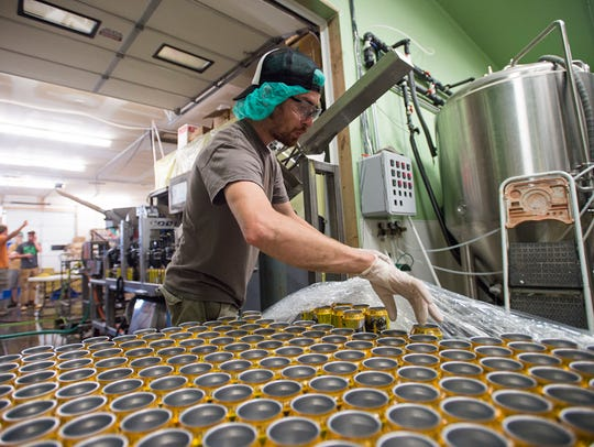 Sean McCarthy loads the canning line at High Hops Brewery