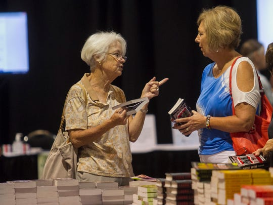 Bonnie Hogan and Sue Geshel talk while shopping for books at the Southwest Florida Reading Festival on Saturday, March 21, 2015, in downtown Fort Myers.