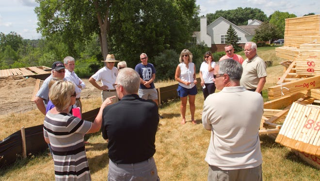Sharon Hazen, front left, with her husband Ralph Hazen at her side, talks to residents and future neighbors about the challenges they have encountered with their subdivision association regarding where their home can be built.