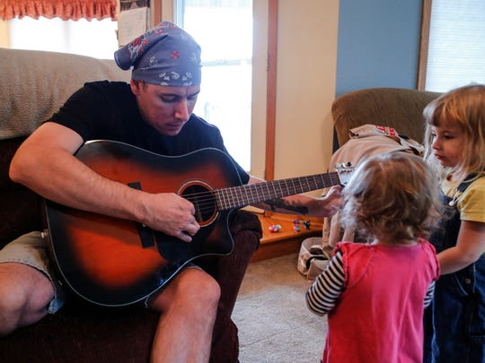 Jim Enos, lead singer of Stutterin' Jimmy and the Goosebumps tunes his guitar while daughters Iris, 1, and Lily, 3, watch at their home in Indianola Wednesday, Nov. 18. 2015.