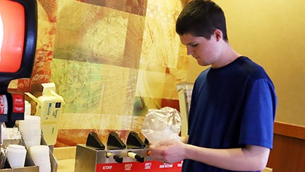 Ethan Howard works at the sods station refilling lids, napkins and straws at Arby's.