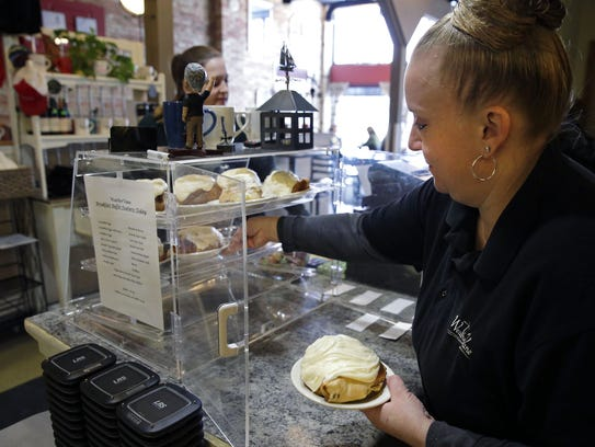 Dawn Kimball puts cinnamon rolls in a case at the WeatherVane