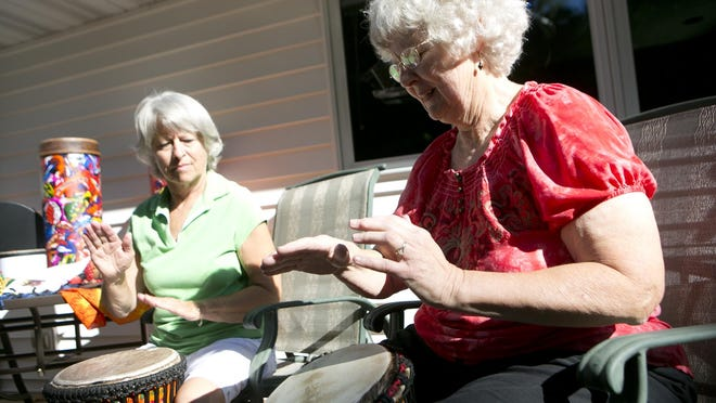Sue Mitchell of Port Edwards, left, and Judy Miller, right, play a Djembe drum and a Dombek drum, respectively, Tuesday at Miller's house in Port Edwards.