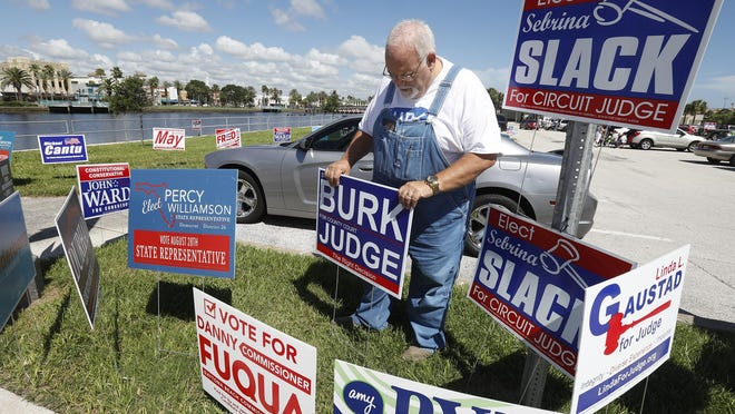 Steve Burk sets-up a campaign sign on City Island in Daytona Beach before the August primary. Like many of the names on the signs posted here, Burk fell short of the votes he needed.