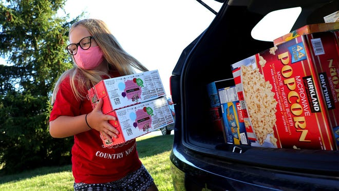 Reese Johnson, 9, helps unload groceries on Aug. 20 that will feed hungry students in the Jonathan Alder school district through Hope's Lantern, a group run by four families.