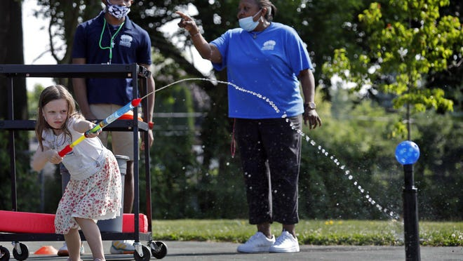 Victoria McKinley uses a water to try knocking a ball  off its stand at the Barnett Recreation Center on June 19. Columbus Parks and Rec has extended programs into the fall.