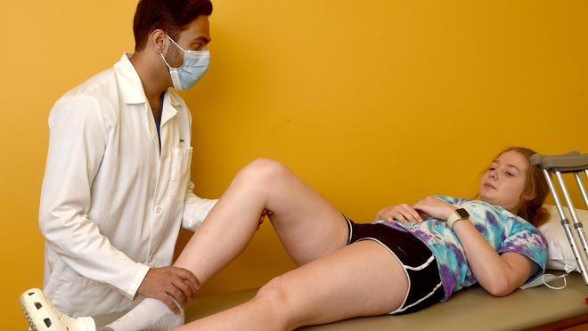 Shawn Sahota, a physician in sports medicine and arthroscopy at the Columbia Orthopaedic Group, examines Sarah Knollmeyer's knee that she injured playing volleyball. The group received a $2 million PPP loan, which has allowed it to retain 165 jobs during the pandemic.