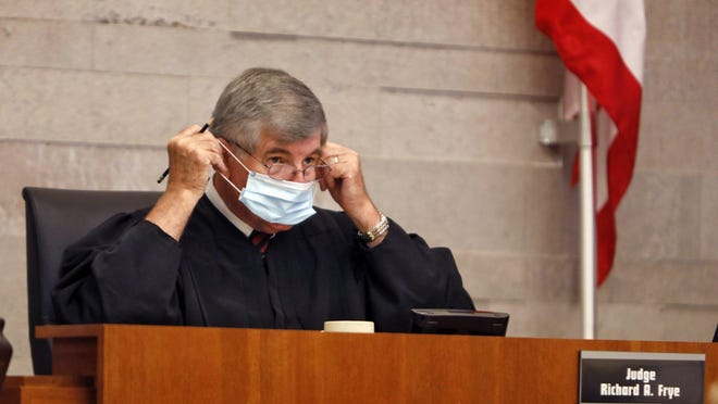 Judge Richard A. Frye adjusts his mask after asking a question during a trial in his Franklin County Common Pleas courtroom in 2020.