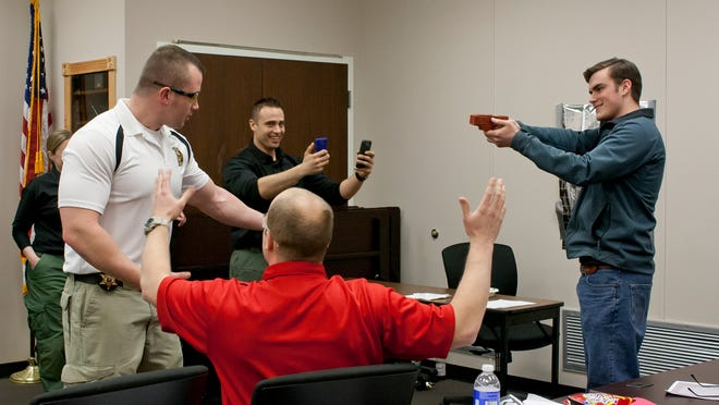 From left clockwise, Deputy Matthew Haselman, Officer Amaro, Ithaca High School Senior Cameron Burbank and Cornell Officer Joe Canzano, seated, act out a scenario at the Citizens Police Academy. Burbank is playing the role of an officer and is holding a mock taser.