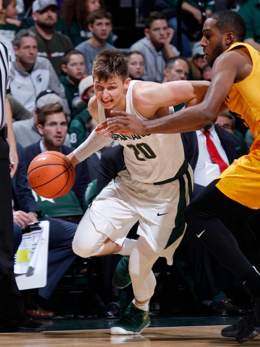 Michigan State's Matt McQuaid, left, drives against Long Beach State's Barry Ogalue during the second half of an NCAA college basketball game, Thursday, Dec. 21, 2017, in East Lansing, Mich. Michigan State won 102-60. (AP Photo/Al Goldis)