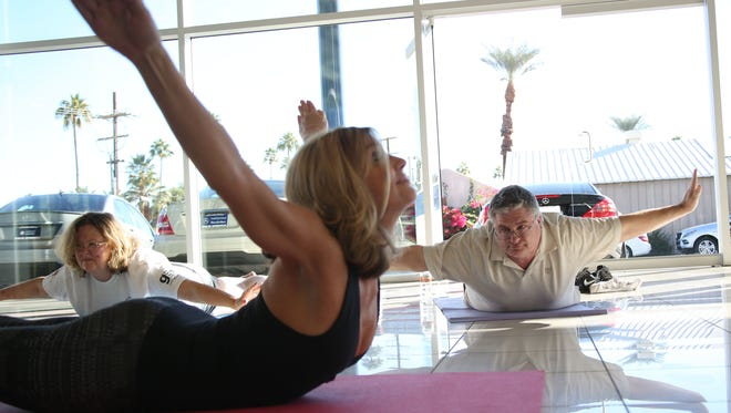Ann Marie Palma, owner of Bikram Yoga Palm Desert studio, leads a class at Mercedes-Benz of Palm Springs during one of the events for the Palm Springs International Health & Fitness Festival.