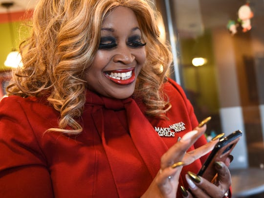 Linda Lee Tarver searches her phone on Wednesday, Dec. 28, 2017 at a coffee shop in downtown Lansing to find photos of herself with President Donald Trump. Tarver is the president of the Republican Women's Federation of Michigan.