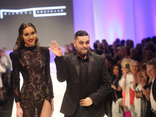 Coachella Valley's own, Michael Costello greets the crowd after his presentation of his designs at the 2015 Fashion Week at El Paseo on March 25, 2015.