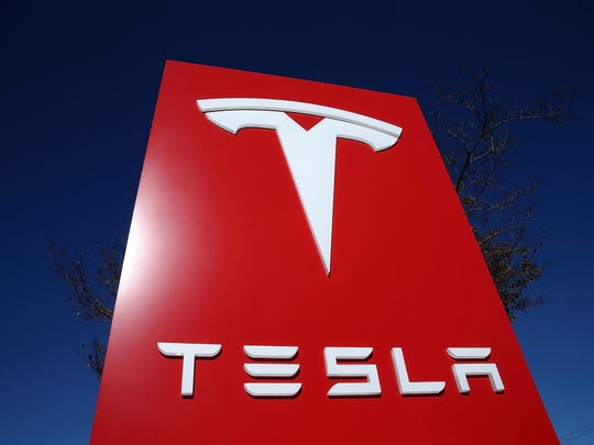 A sign is posted at a Tesla showroom in Palo Alto, Calif.
