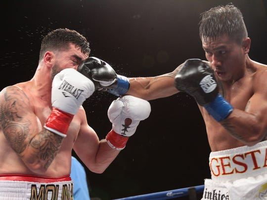 Super Lightweights Mercito Gesta, in blue tape on gloves and Carlos Molina with red tape on gloves during their main event bout at Fantasy Springs Resort Casino during Golden Boy night of boxing at the casino on April 30, 2015. The bout was declared a split draw.