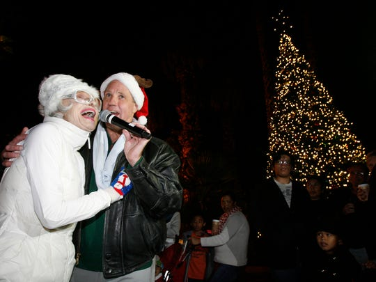 "Carol Channing and Palm Springs Mayor Steve Pougnet say ""Merry Christmas"" to the crowd congregated for the Christmas Tree at Frances Stevens Park during the annual Palm Springs Tree Lighting Ceremony on December 5, 2013."