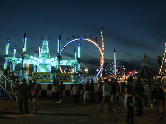 Fairgoers enjoy the numerous rides, games, exhibits, and food ve