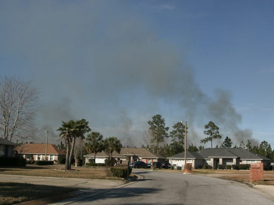 Smoke from a prescribed burn between N. Blue Angel Pkwy. and Lillian Hwy. by the Florida Division of Forestry on Wednesday can be seen behind homes on Southwind Circle.  A dirt firebreak was created between the homes and the trees near the burn.