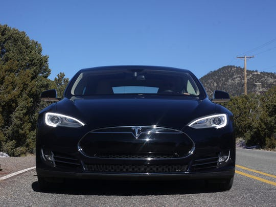 A current-model Tesla is seen from the front end of