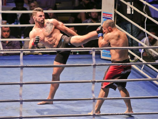 Frank Carrillo, blue gloves, and Mike Perry, red gloves, fight each other Friday night during Island Fights 37 at the Pensacola Bay Center. Perry knocked Carrillo out in the first round for the win.