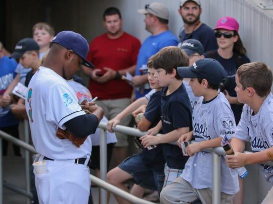 """Pensacola's El'Hajj Muhammad signs autographs before the game Thursday night. The Blue Wahoos played as the Pensacola Mullets during a special """"What if?"""" event representing one of the names that was originally suggested for the team."""
