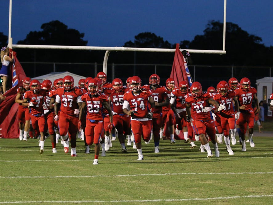 The Eagles run onto the field Friday night at Pine Forest High School.
