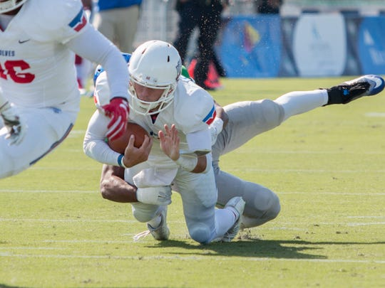 West Georgia quarterback Willie Candler (7) gets taken down from behind by West Florida's Asante Griffin (26) during the last game of the inaugural 2016 season for the Argos Saturday afternoon at Blue Wahoos Stadium.