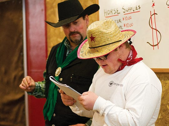 Kelby Woolf (right), reads a story he wrote while Ark Arena Manager Ed Ulrich looks on at the Ark Equestrian Center in Laramie, WY.
