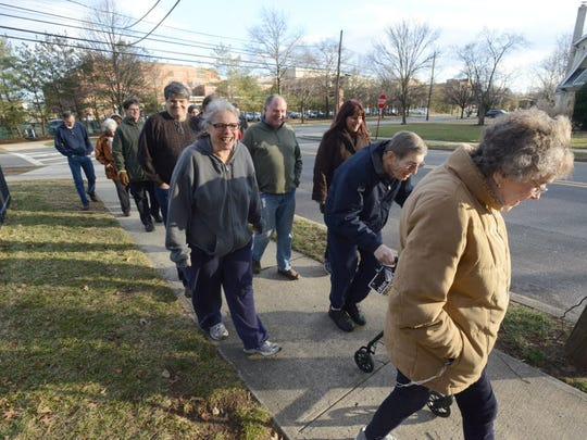 Members of Concerned Residents of Ridgewood, who gathered Sunday to discuss the long fight to prevent The Valley Hospital from expanding, walk past the hospital after their meeting.