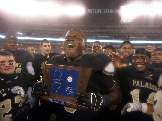 Jabrill Peppers celebrates with the victory trophy after Paramus Catholic defeated St. Peters for theNon-Public Group Four State Championship game at met MetLife Stadium Dec. 6, 2013.