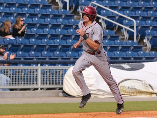Troy's Brandon Lockridge scores on an RBI single hit by teammate Chase Smartt Sunday afternoon during the last day of the Cox Diamond Invitational at Blue Wahoos Stadium.